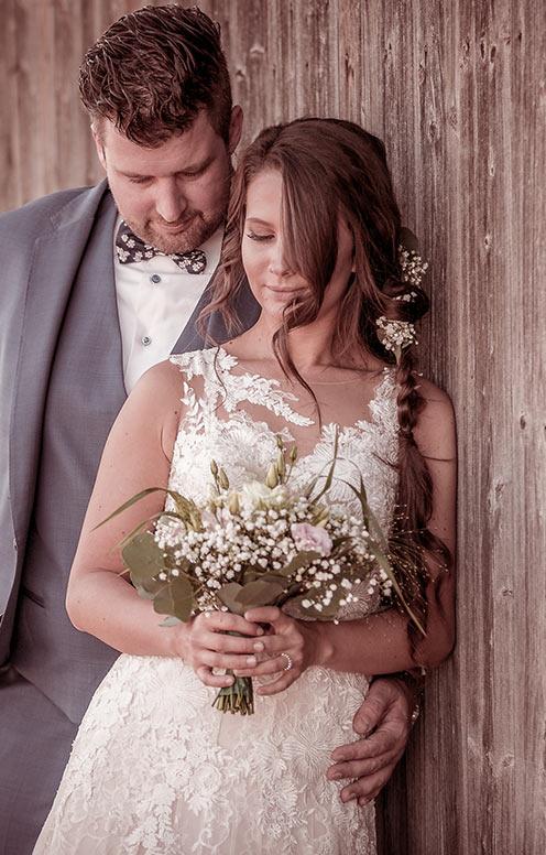 Hochzeitspaar an Holzwand