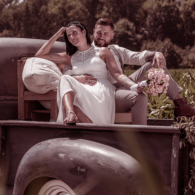 Hochzeitspaar beim fotografieren auf einer Ladefläche von einem Picup