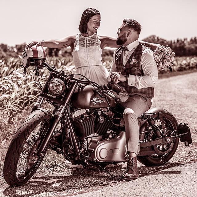 Hochzeitspaar bei einem Shooting mit einer Harley-Davidson. Bräutigam sitzt und braut ist angelehnt und schaut dem Bräutigam tief in die Augen.