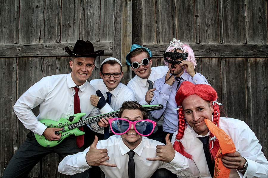Hochzeitsgäste haben Spaß vor einer Fotobox