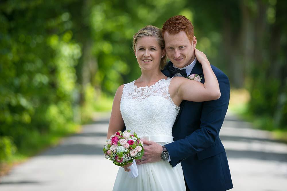 Hochzeitspaar vor einer Baumallee