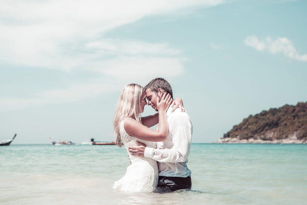 Hochzeitspaar am Stand halb im Wasser in Thailand