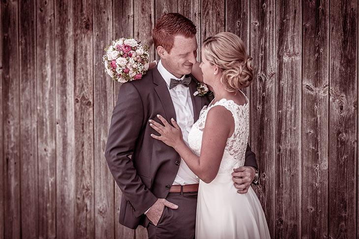 Hochzeitspaar verliebt mit einem Blumenstrauss an einer Holzwand