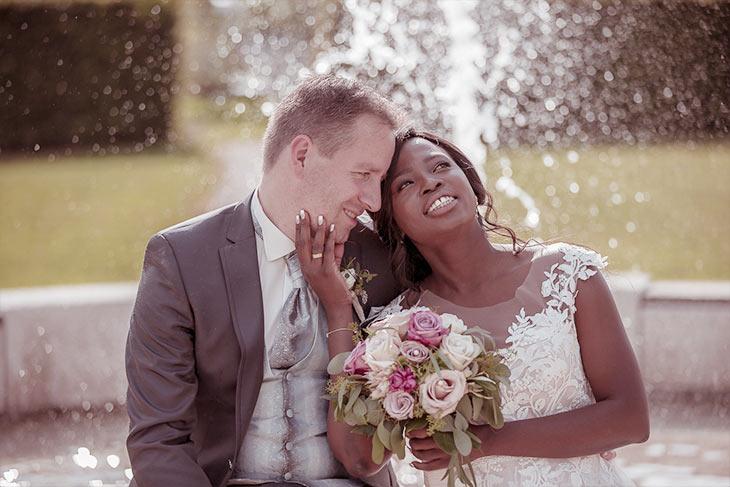 Brautpaar sitzt mit einem Blumenstrauss an einem Springbrunnen