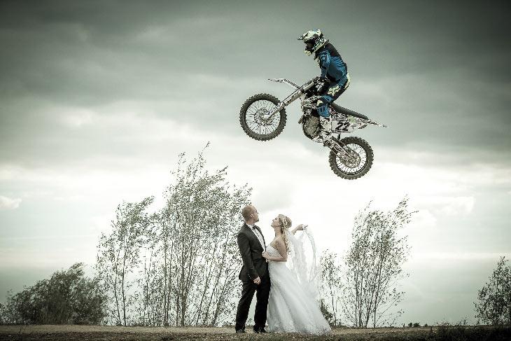 Hochzeitspaar bei einem After Wedding Shooting, Motocross Mottorad spring über das Paar