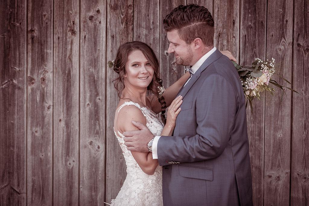 Hochzeitspaar vor einer Holzwand